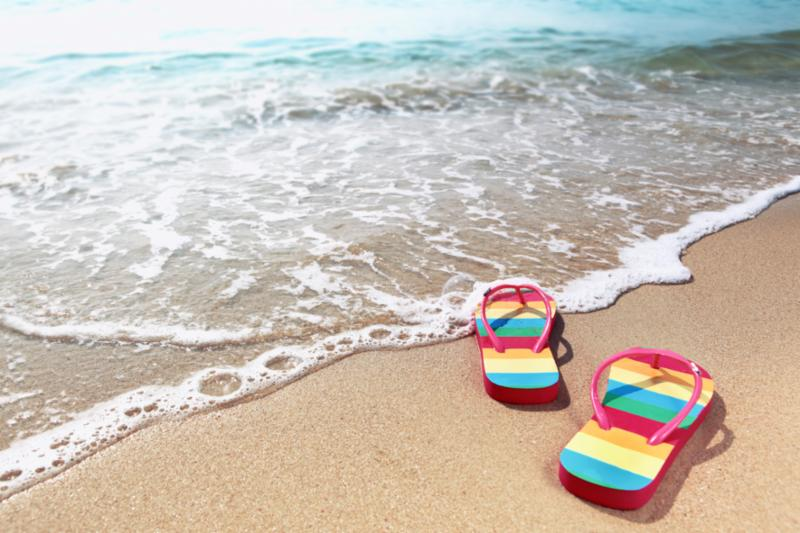 Rainbow flip flop sandals on the sand at the edge of an ocean