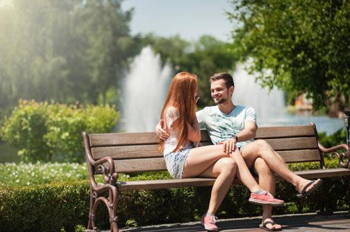 A girl and guy sit on a bench next to each other outside and are smiling