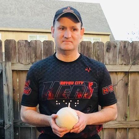 Doug Biggins wearing his Heat baseball uniform and holding a beep baseball