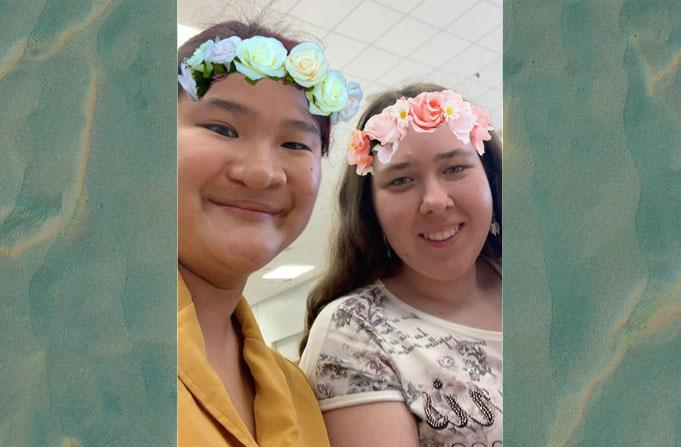 Nora and Jennifer smiling with a flower filter on the photo