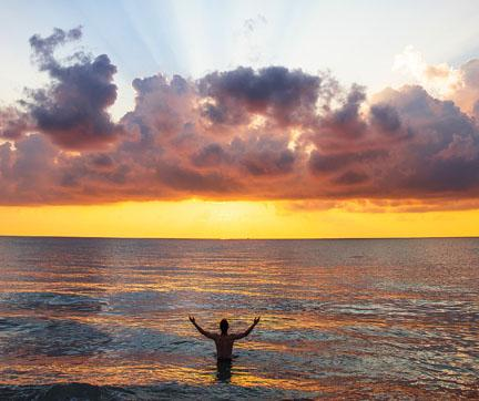 A person standing in the ocean with their hands up to the sky and a sunset in the background