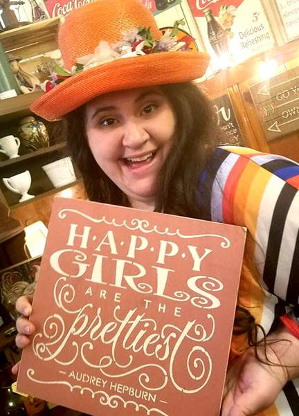Kirstianna with a hat on and bright colors holding a sign that says Happy Girls are the Prettiest