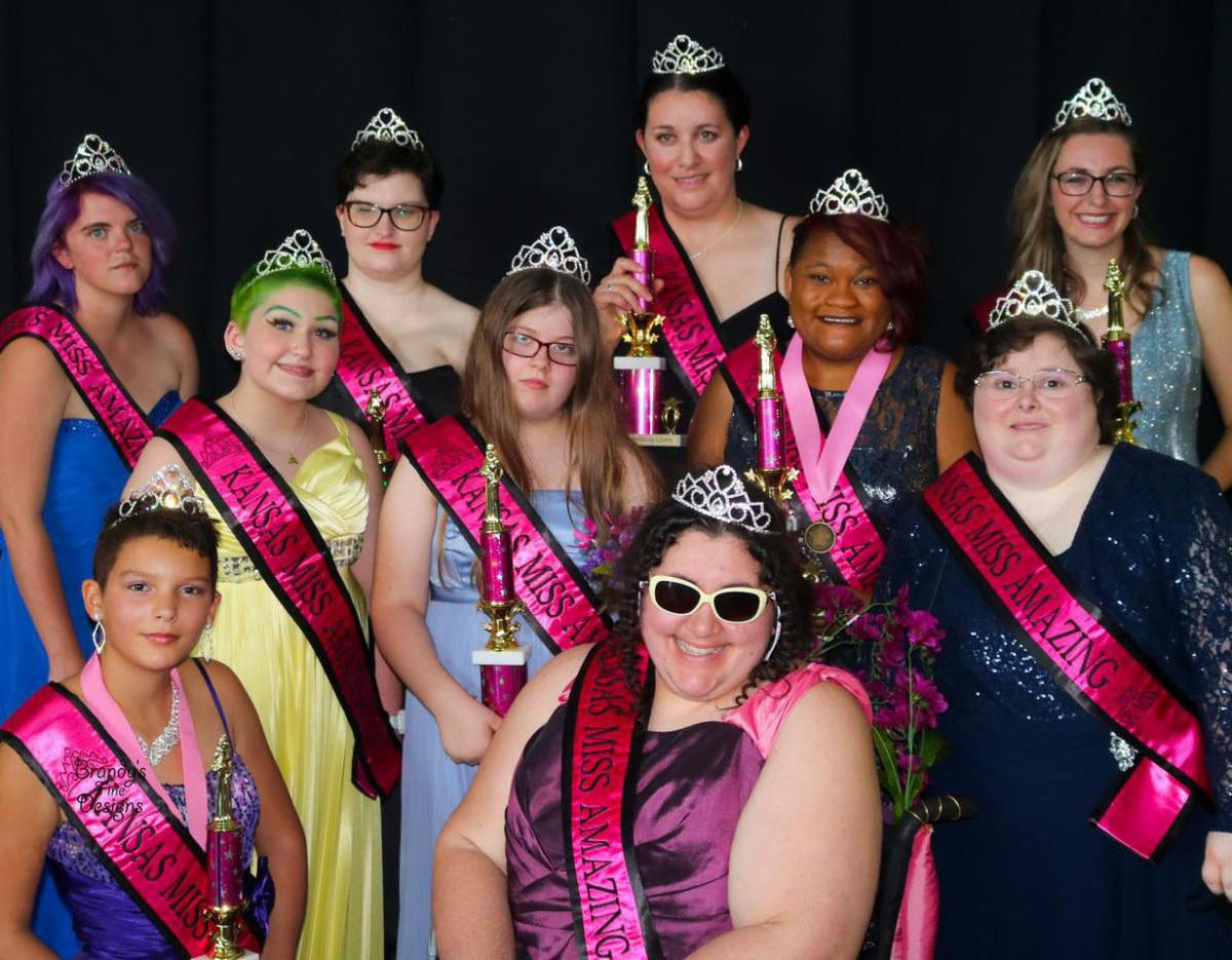 A group of 10 females with various disabilities taking a group picture wearing crowns and sashes