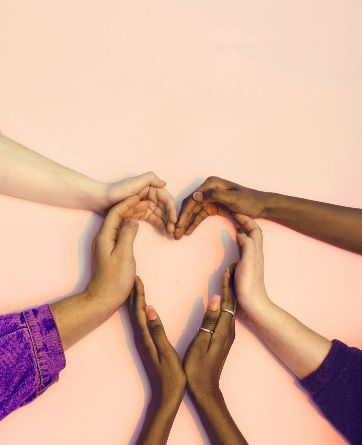Hands with different skin color making the shape of a heart