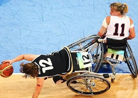 Sarah Castle playing wheelchair basketball and her opponent is falling over to catch the basketball