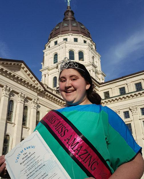 Kirstianna wearing crown and sash standing in front of the State Capital building holding a proclamation
