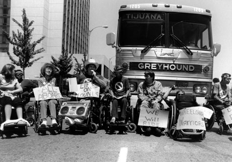 A group of people who are wheelchair users hold protest signs and sit in front of a Greyhound bus