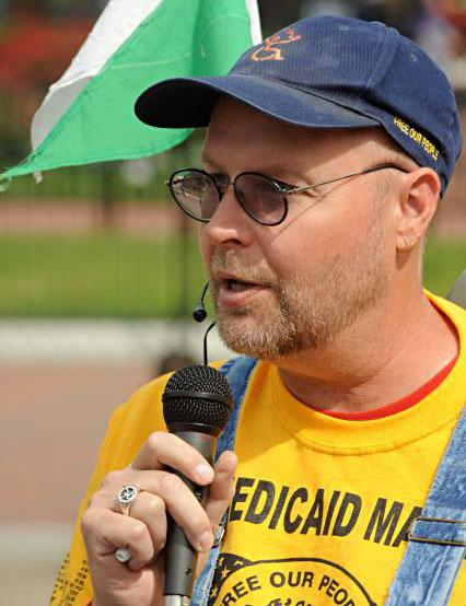 Mike Oxford speaks into a microphone at an ADAPT event. He is wearing an ADAPT hat and shirt.