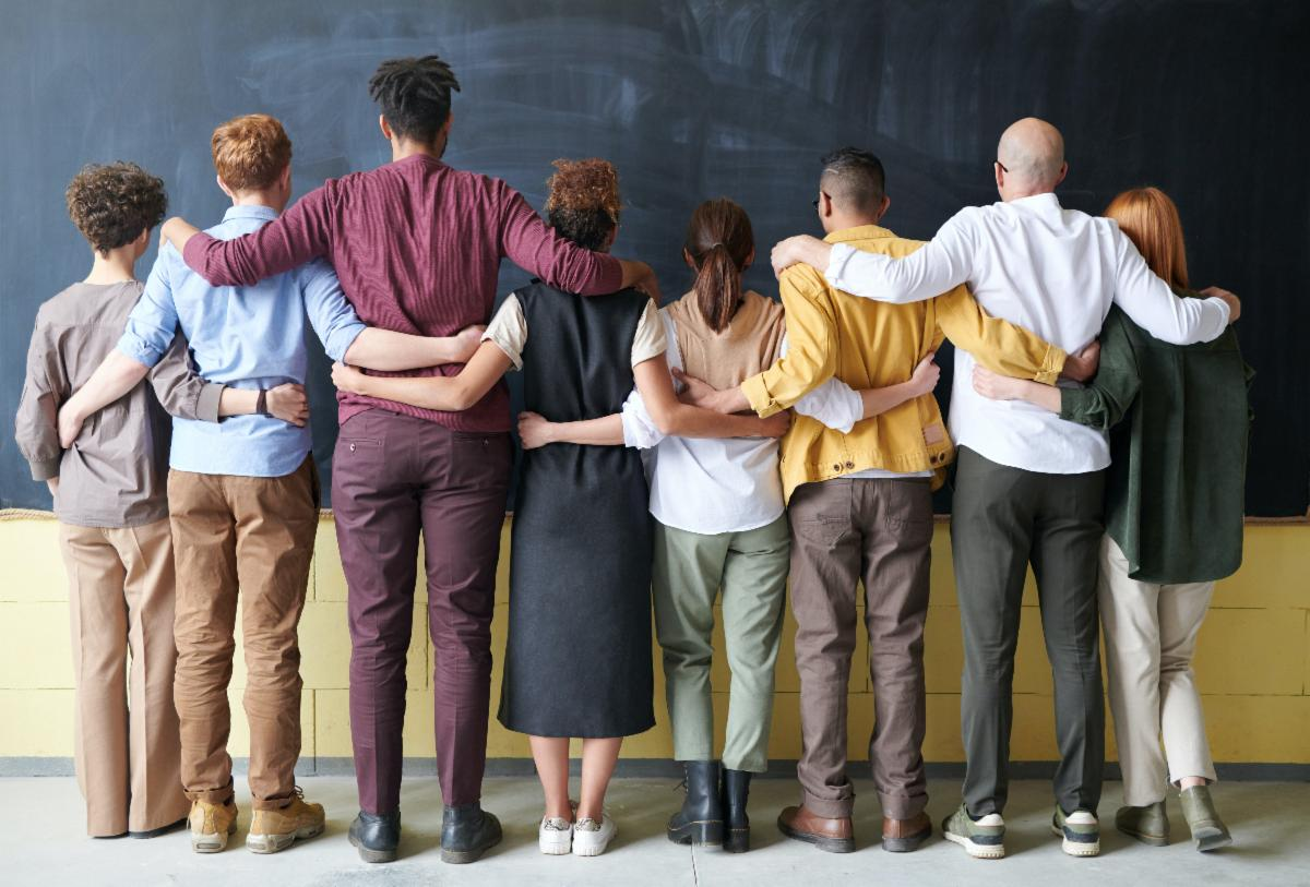 The backs of a group of 8 people of different races with their arms around each others shoulders