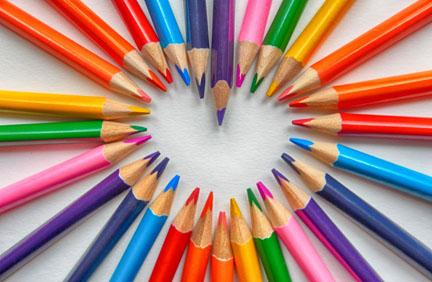 A rainbow of colored pencils in the shape of a heart
