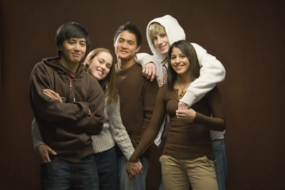 A group of diverse teens in a group_ holding hands_ and putting their arms on each others shoulders