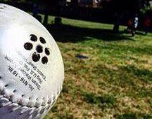 A beep baseball sitting on grass