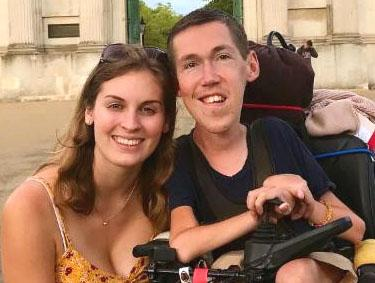A guy who is wheelchair mobile takes a happy picture with his girlfriend who is able bodied
