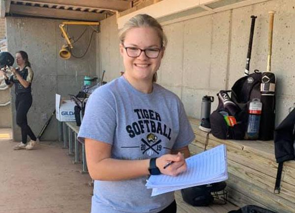Madison Zimmerman in a softball dugout writing information on a sheet