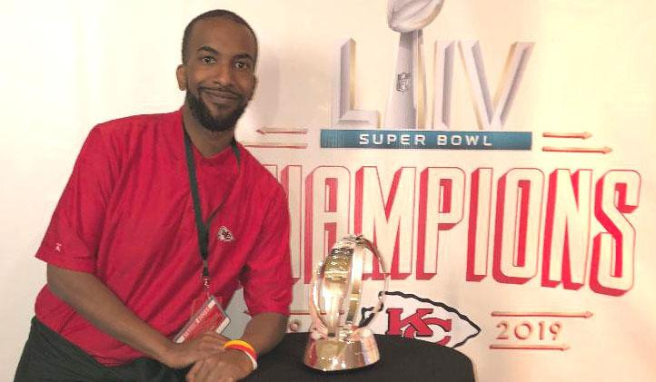 Phillip stands next to a glass football trophy in front of a sign that says KC Chiefs Super Bowl Champions 2019