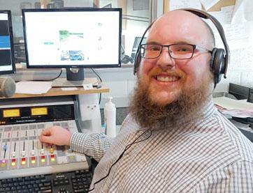 Tagan Trahoon wearing headphones at his job