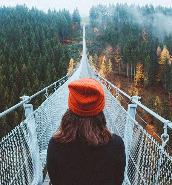 A girl wearing a stocking hat getting ready to walk across a bridge that goes way into the distance high off of the ground