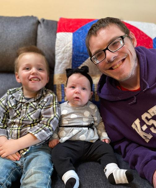 Seth Wagner smiling with two children