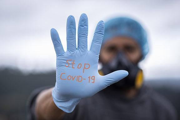 A man wearing a hair net and large mask and glove is putting his hand out and the words Stop COVID 19 are written on the glove