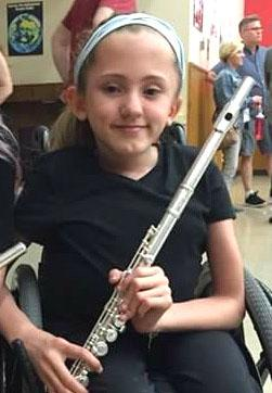 Ariana Hutchinson smiles and holds her flute.