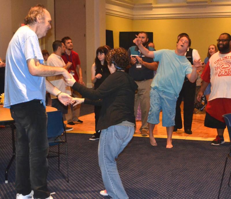 Julia and Roger dance together by holding hands while the KSYLF delegates and staff cheer them on