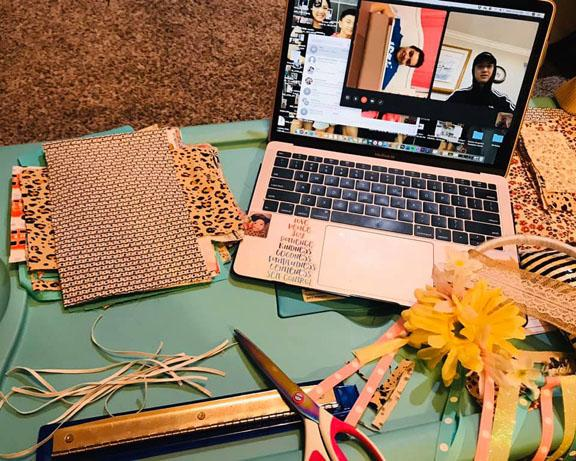 A bunch of things on a desk including a laptop and craft supplies and paper and scissors