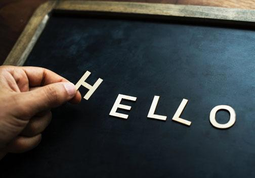 A person's hand is putting letters that spell hello on a board