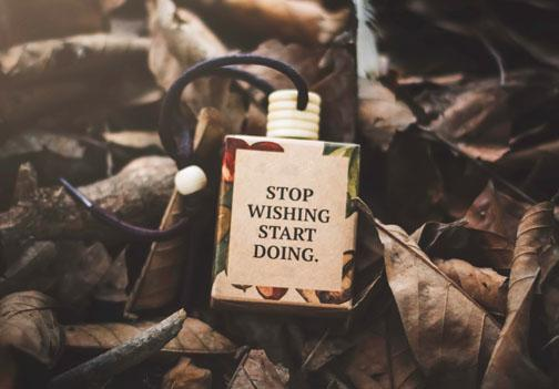 A small necklace laying in leaves and the necklace says Stop Wishing Start Doing