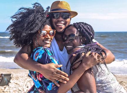 Three people embracing on the beach
