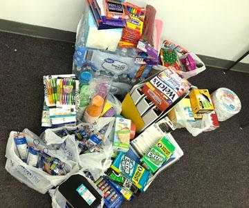 A large pile of donations like markers and notepads and pens and water and food and binders