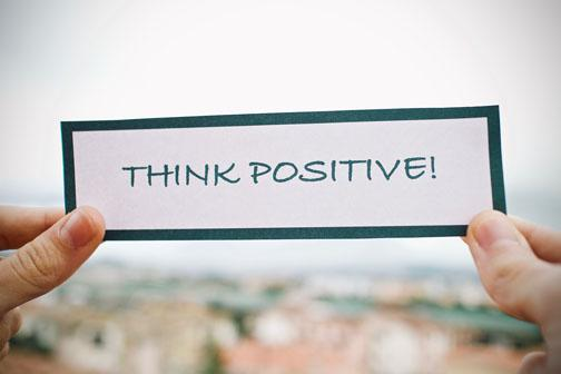 A person holding a sign that says Think Positive