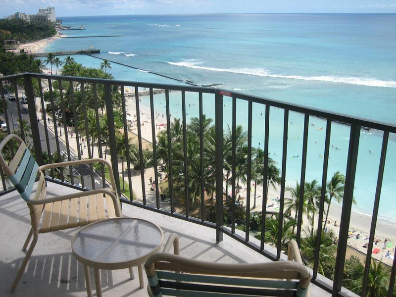 A hotel balcony with sitting chairs overlooks Waikiki Beach in Honolulu Hawaii.