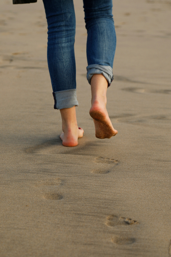 young women on the beach_ foot prints on wet sand_ footsteps on the beach_ one person_ feet and jeans_ horizontal