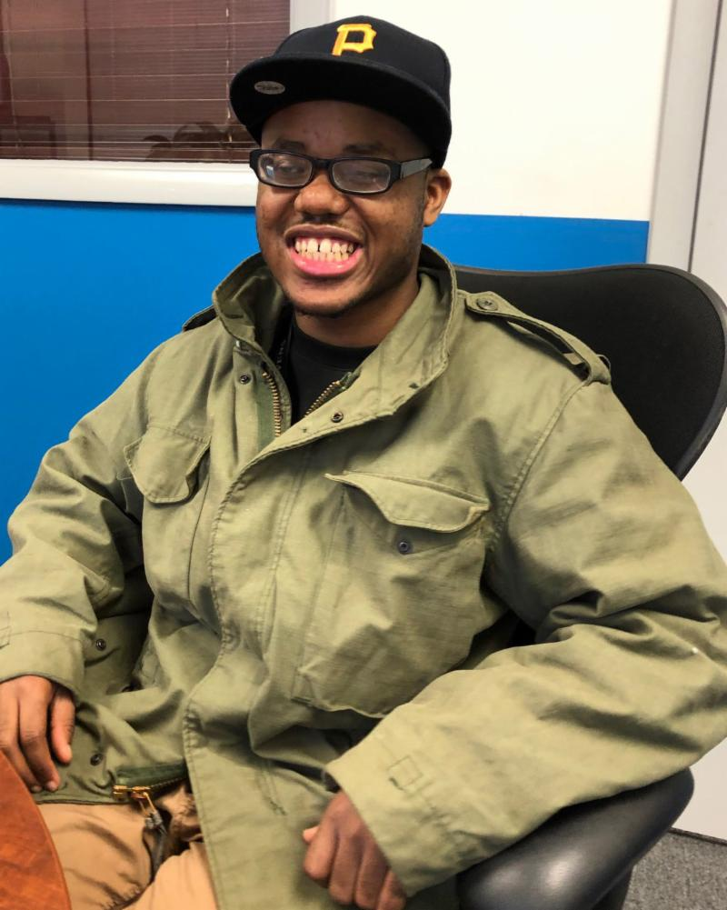 Johnathan a young African American man wearing glasses seated at a conference table smiling at the camera