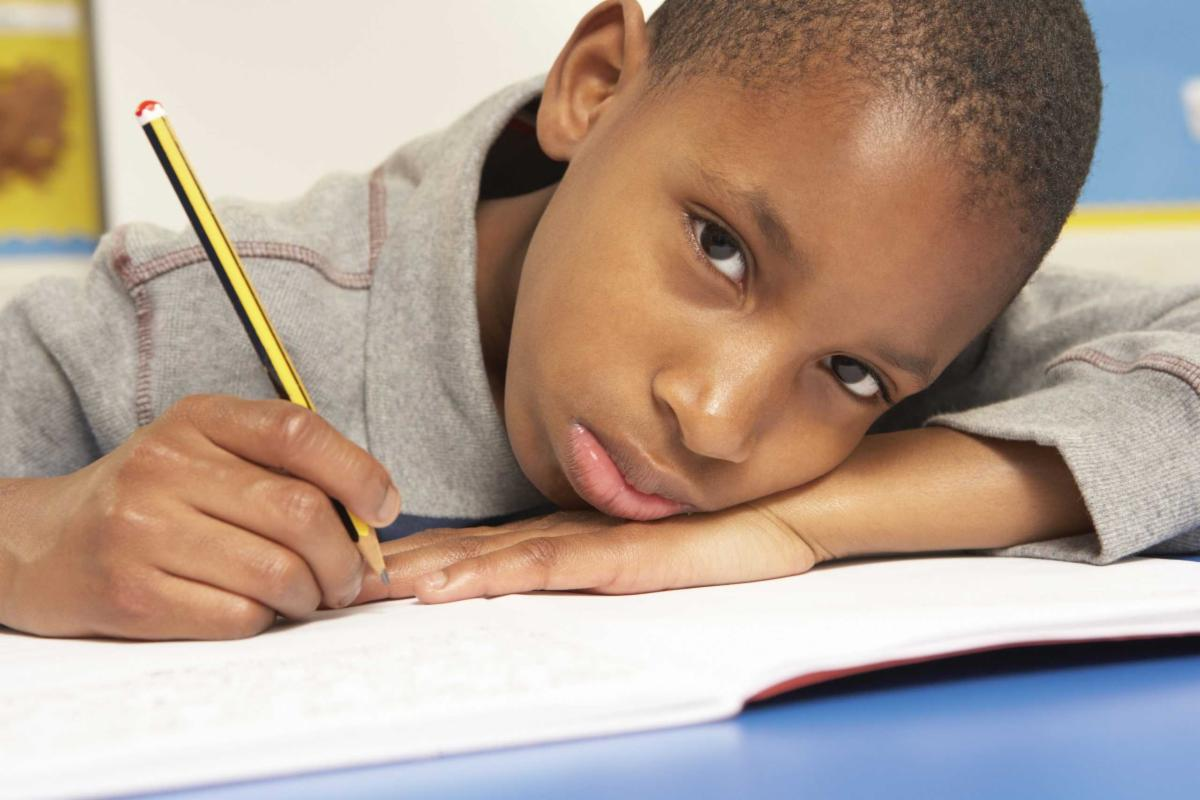 An image of a pouting young boy. He is looking up at the camera as he struggles to do his homework.