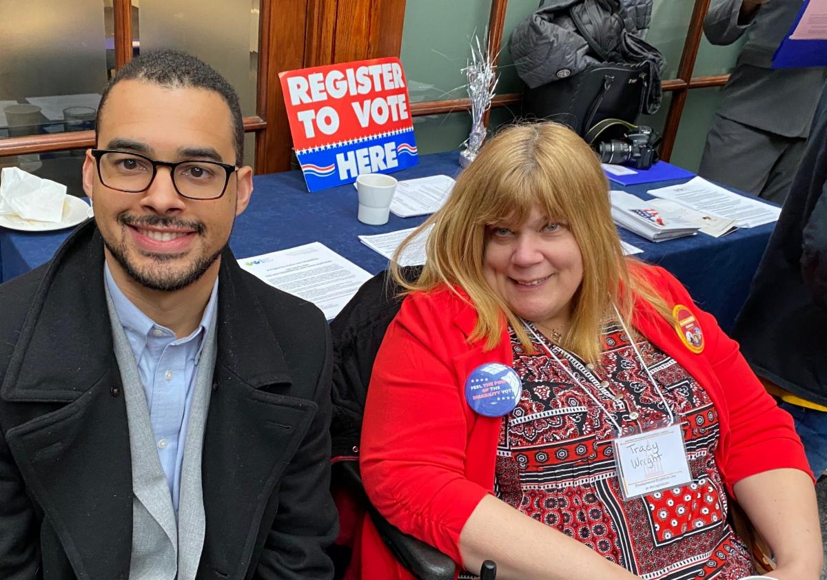 """Image of Ben Jackson, DRM Staff Attorney, and Tracy Wright, DRM Voting Advocate, sitting in front of blue table. Table has papers and pamphlets and a sign that says """"Register to Vote""""."""