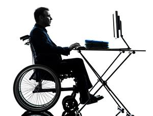 man in wheelchair at desk