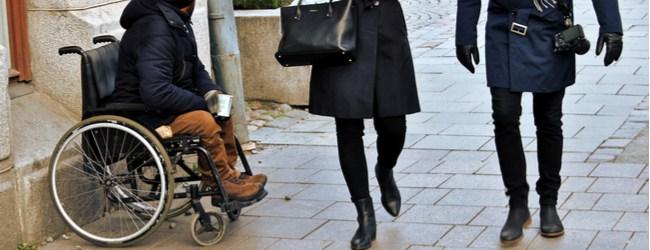 man in a wheelchair panhandling