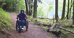 woman in wheel chair on trail in the woods
