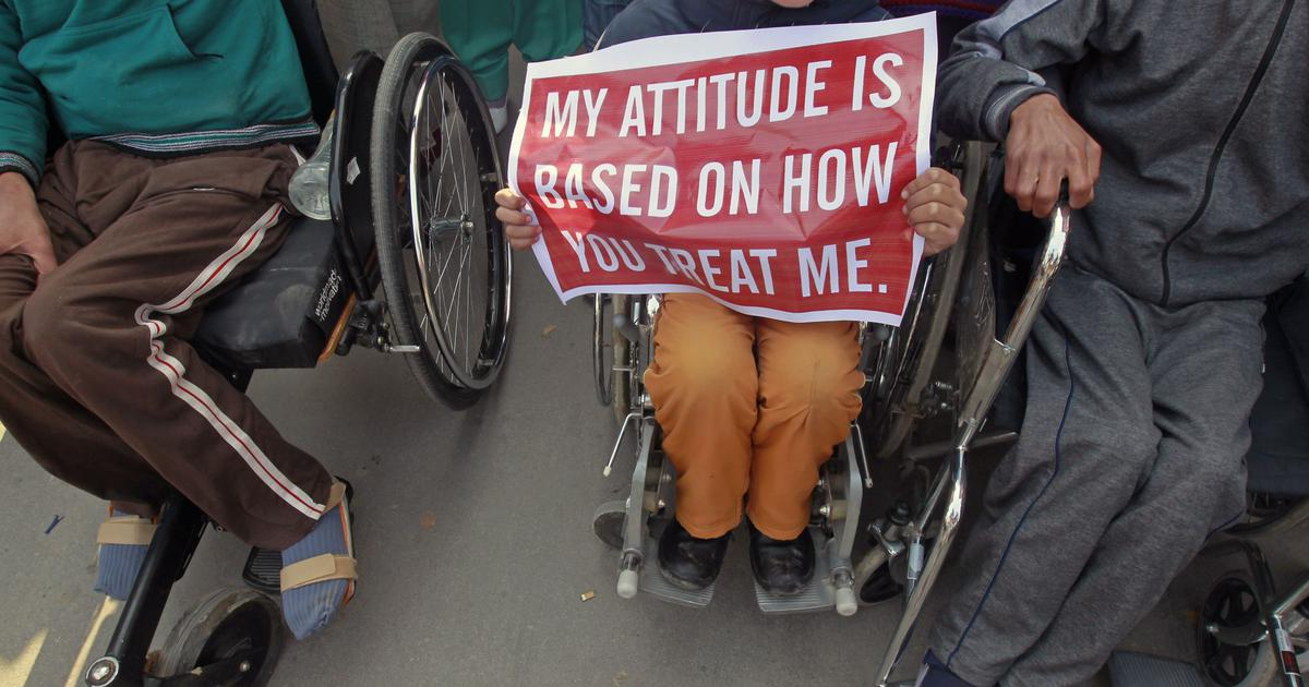 """person in wheel chair holding sign that reads, """"My Attitude is based on how you treat me."""""""