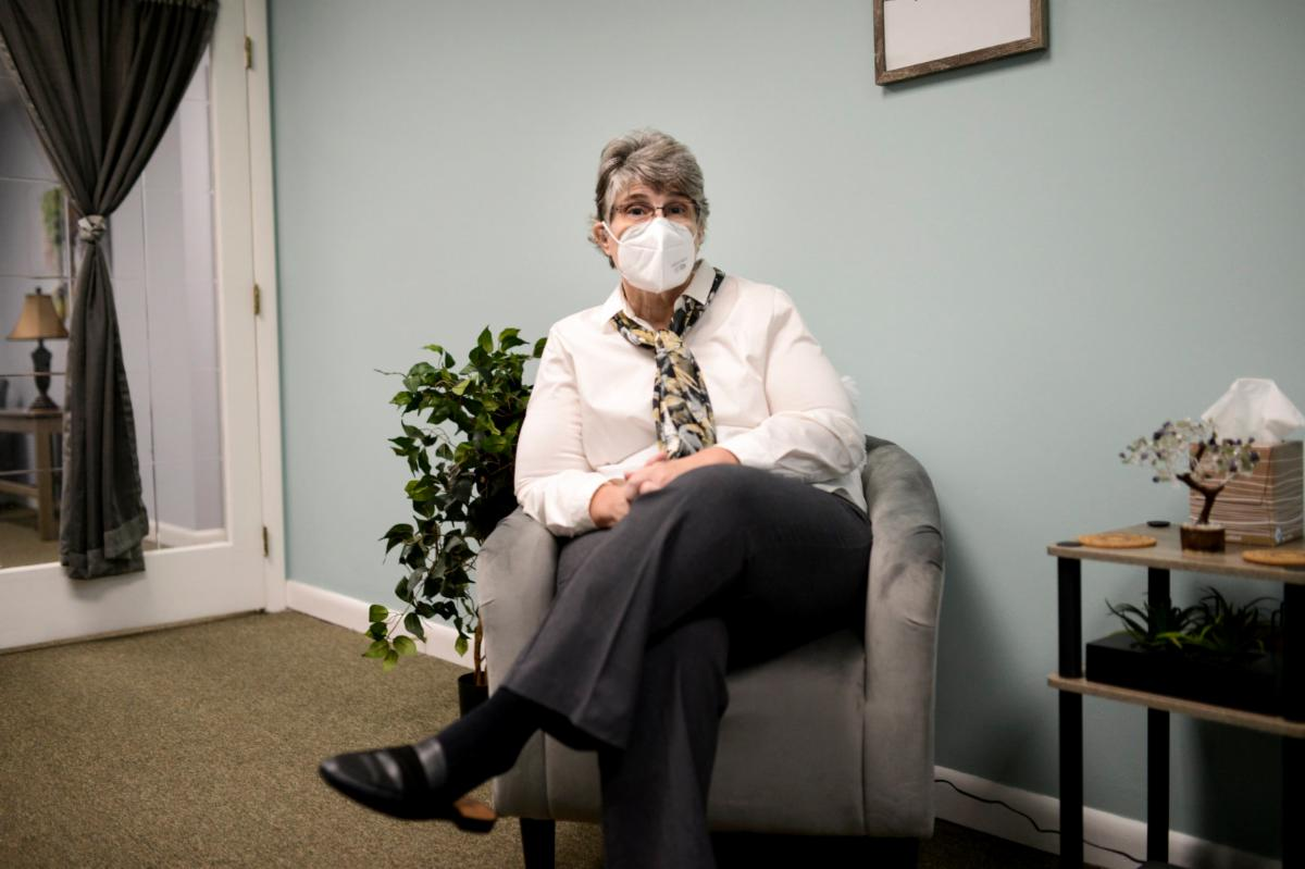 woman seated wearing face mask