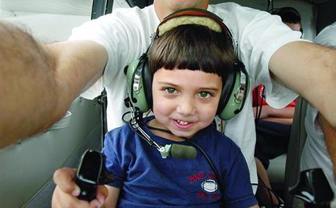 a little boy sitting on a pilot_s lap