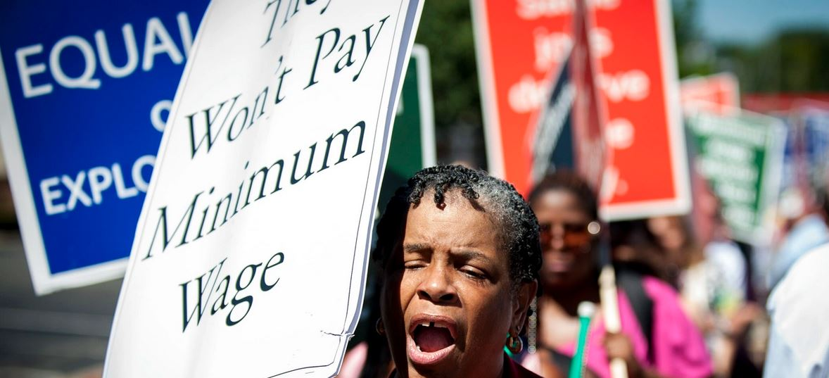 """protestor holding a sign that reads, """"They won't pay minimum wage"""""""