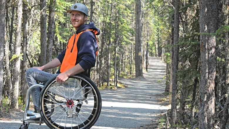 man in wheelchair on a trail in the woods