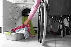 person in wheelchair doing laundry