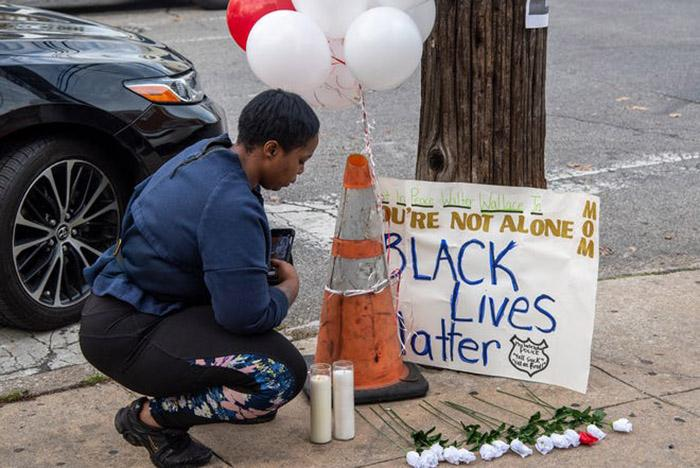 """person kneeling at a vigil site with sign that says """"Black Lives Matter"""""""