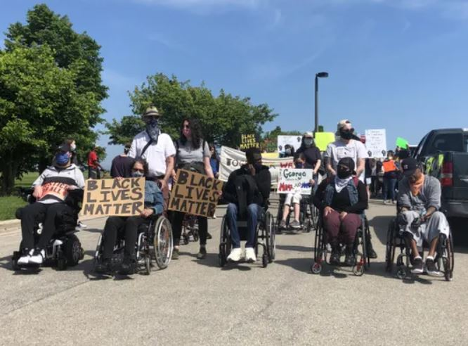 protest lead by people in wheelchairs holding signs _Black Lives Matter_