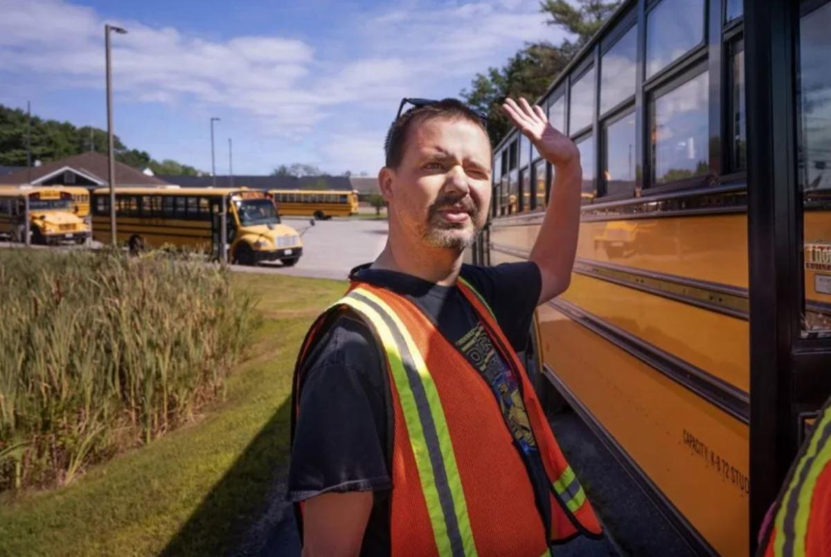 man in an orange safty vest assisting with school busses