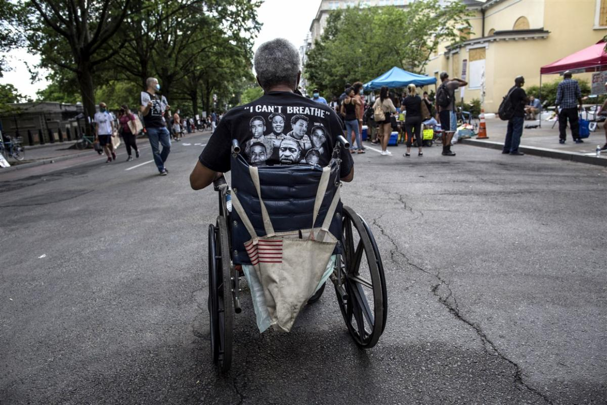 back of a black man in a wheel chair wearing a t-shirt saying _I can_t breath_