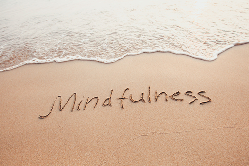 mindfulness concept_ mindful living_ text written on the sand of beach